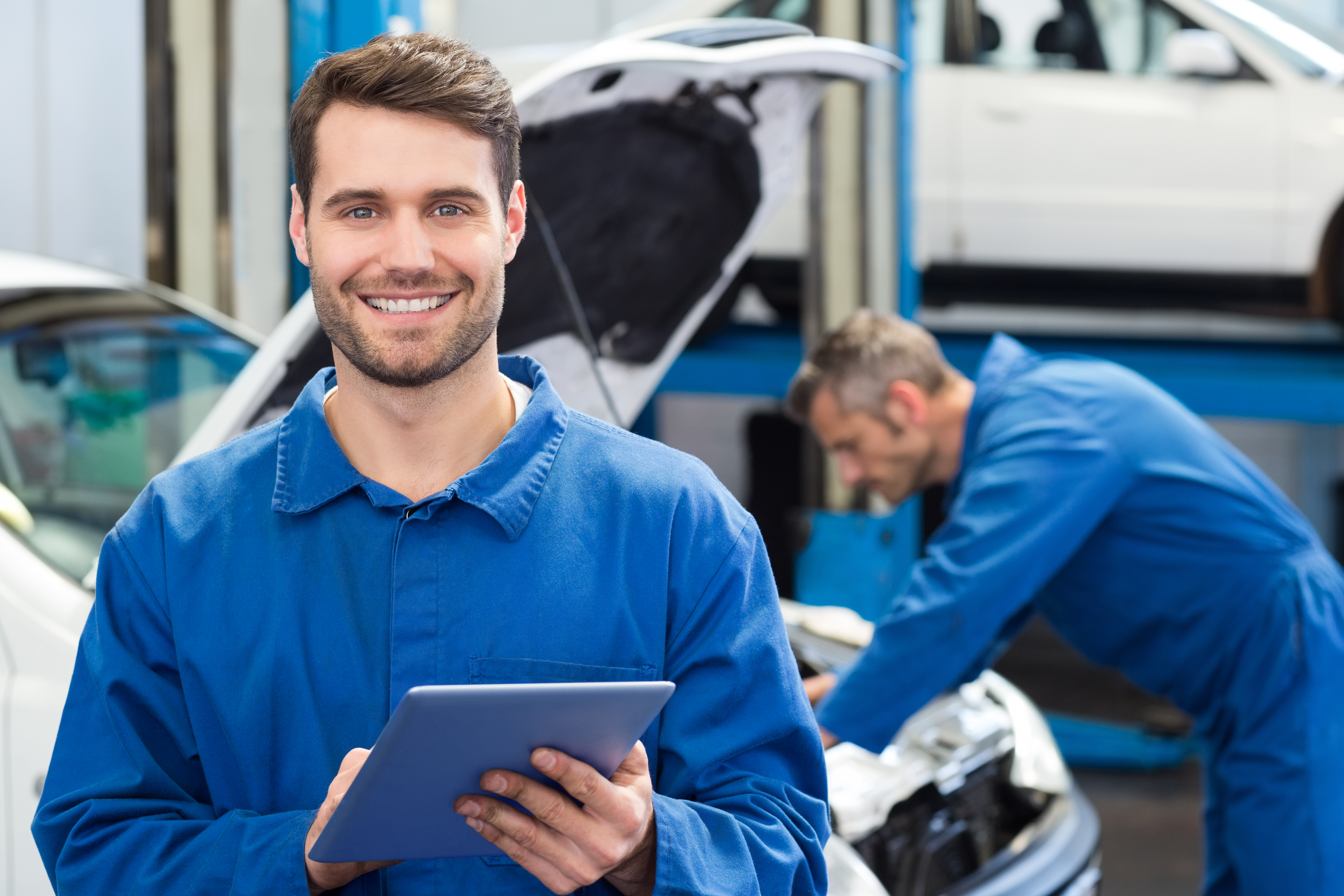 Image of a smiling mechanic using a tablet in a workshop